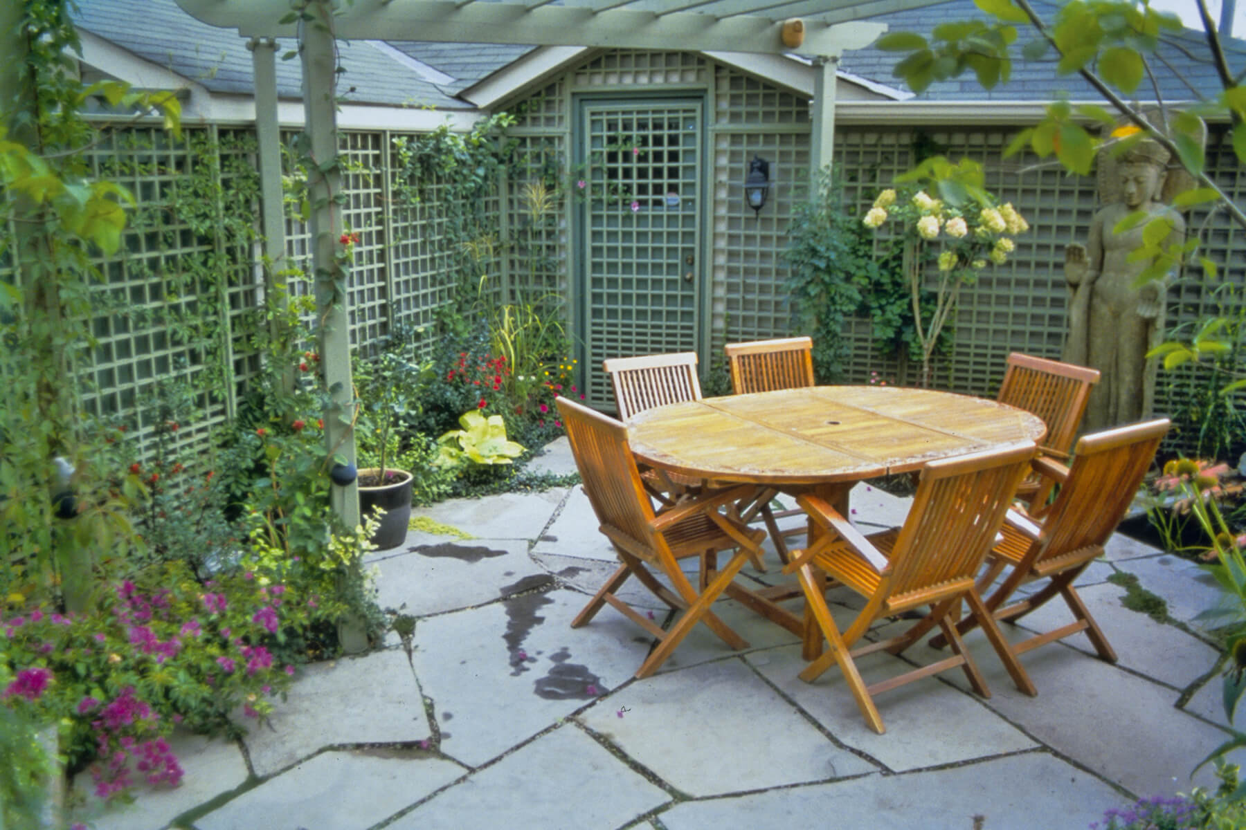 award winning backyard garden with table chairs and lattice