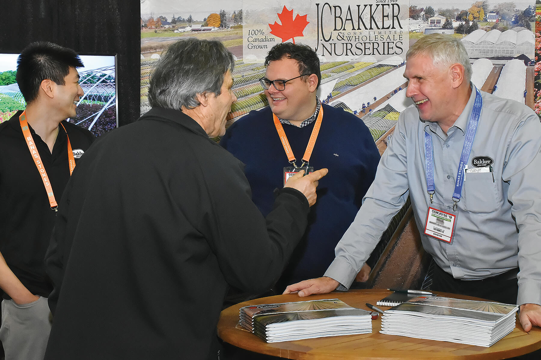 three happy men doing business at a trade show