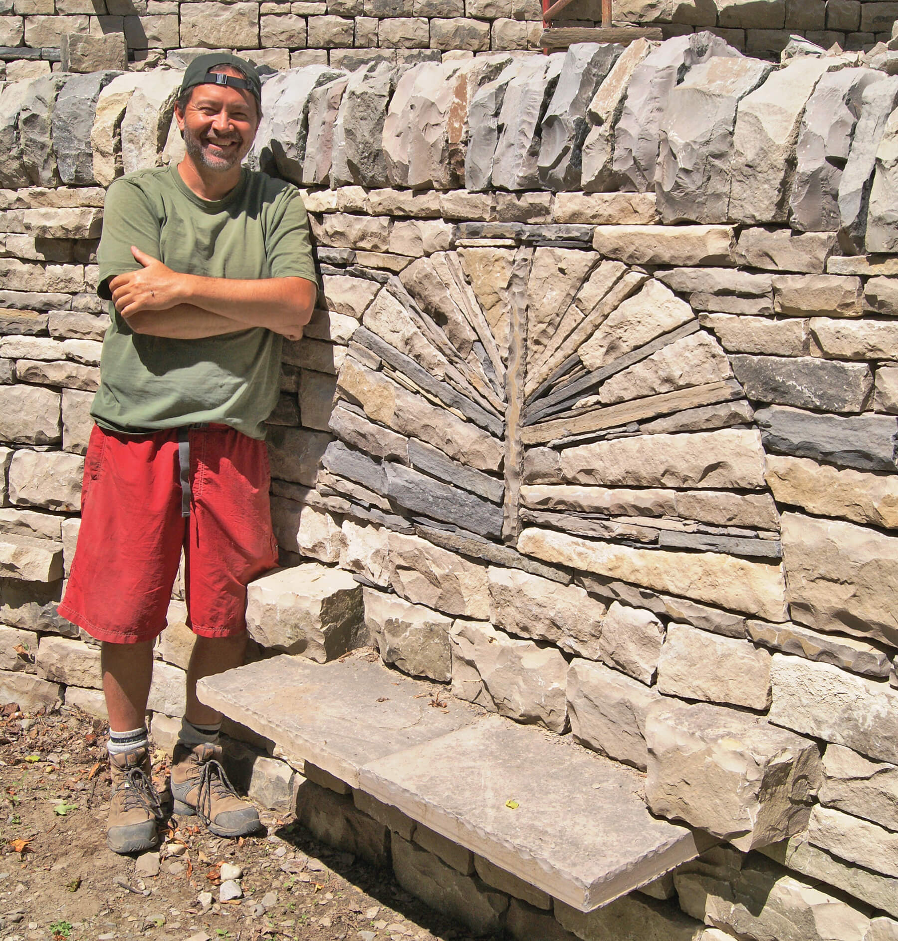 man proudly standing beside a large stone wall with built in bench