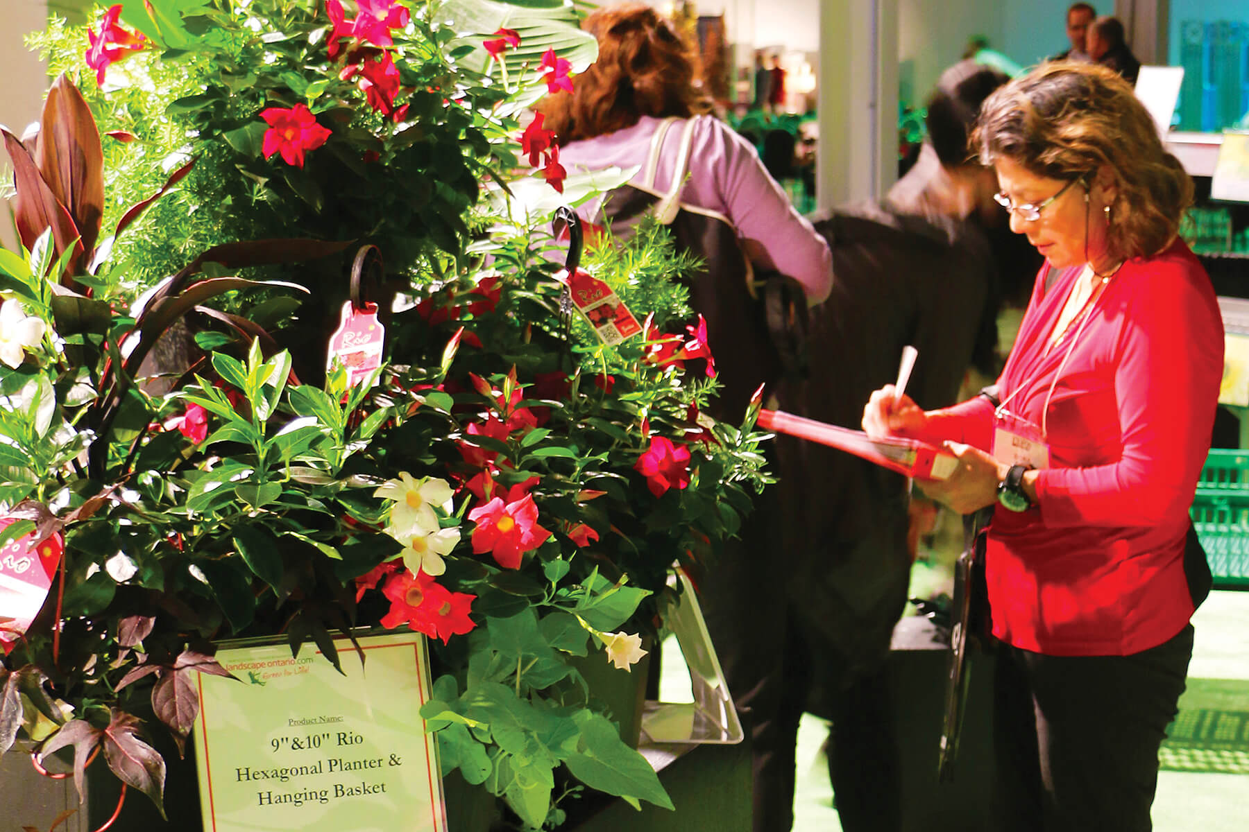 woman with a clipboard evaluating a large floral display