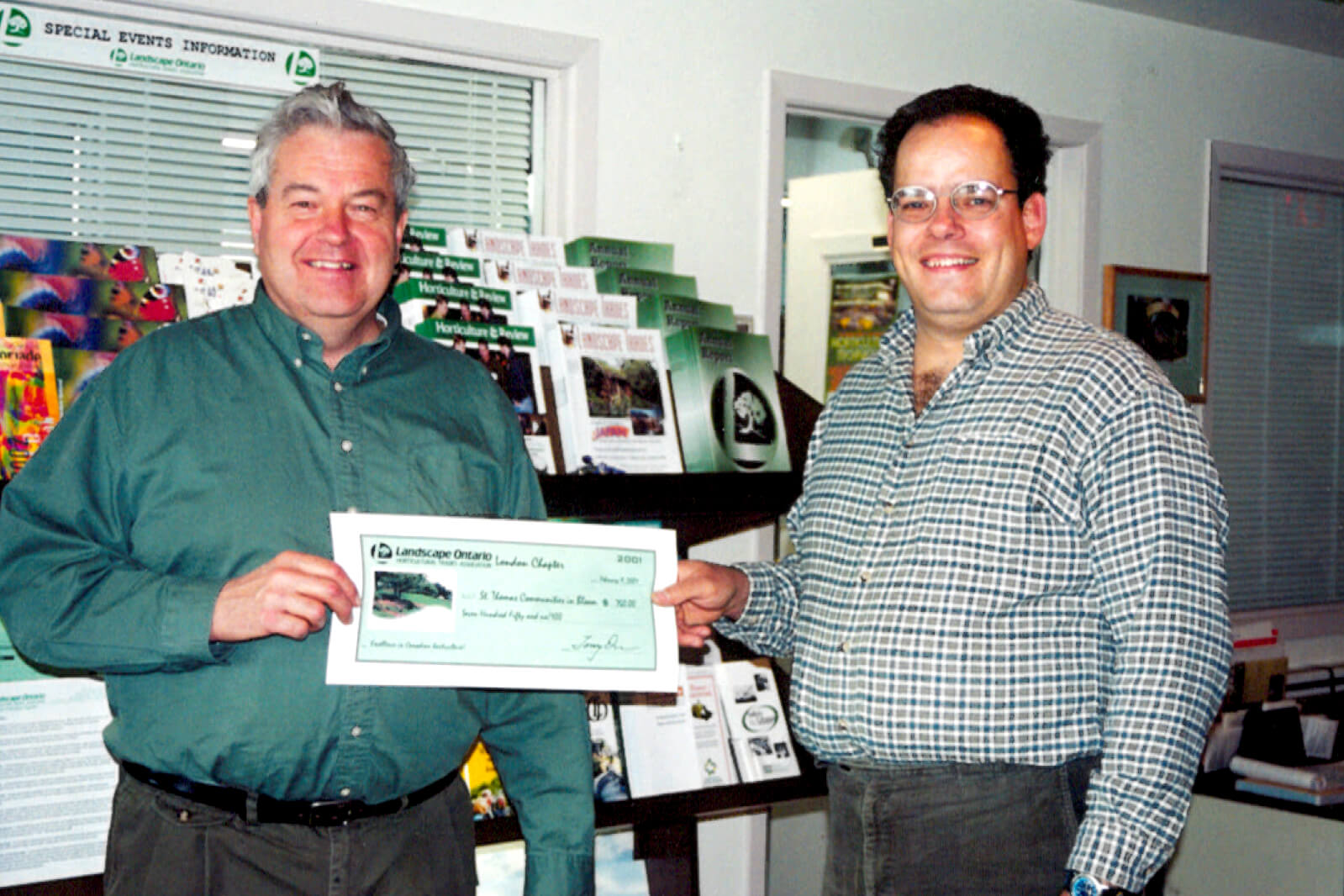 two men holding a cheque
