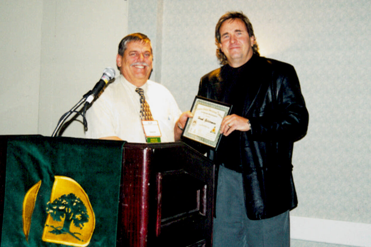 two men at a podium. one accepting a certificate