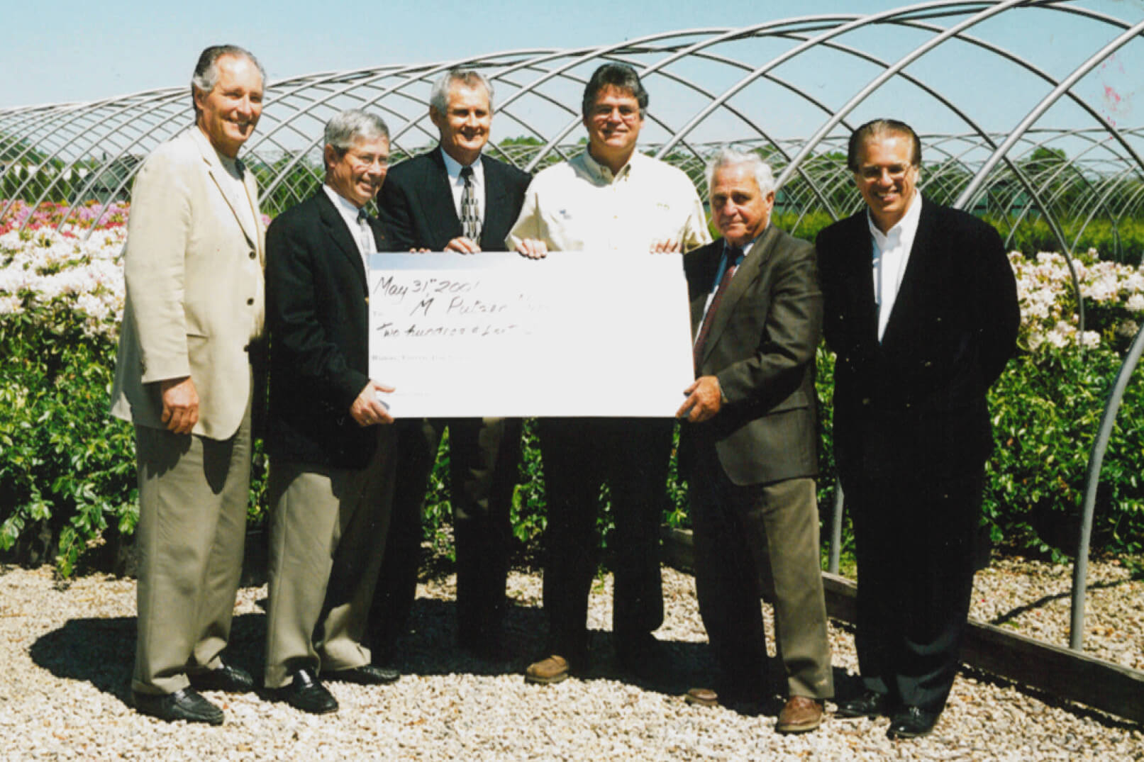 six men holding a cheque in nursery outdoors