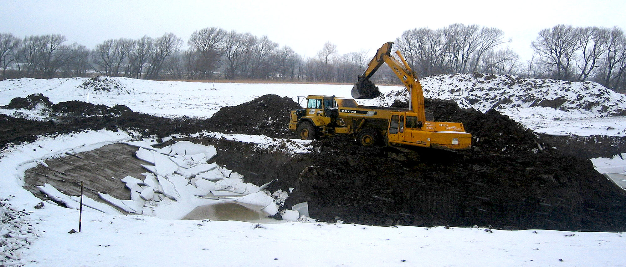 excavator working in a field in winter
