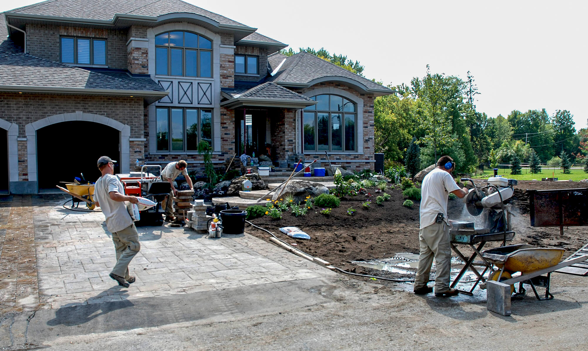 men working on the landscape in the front yard of a home
