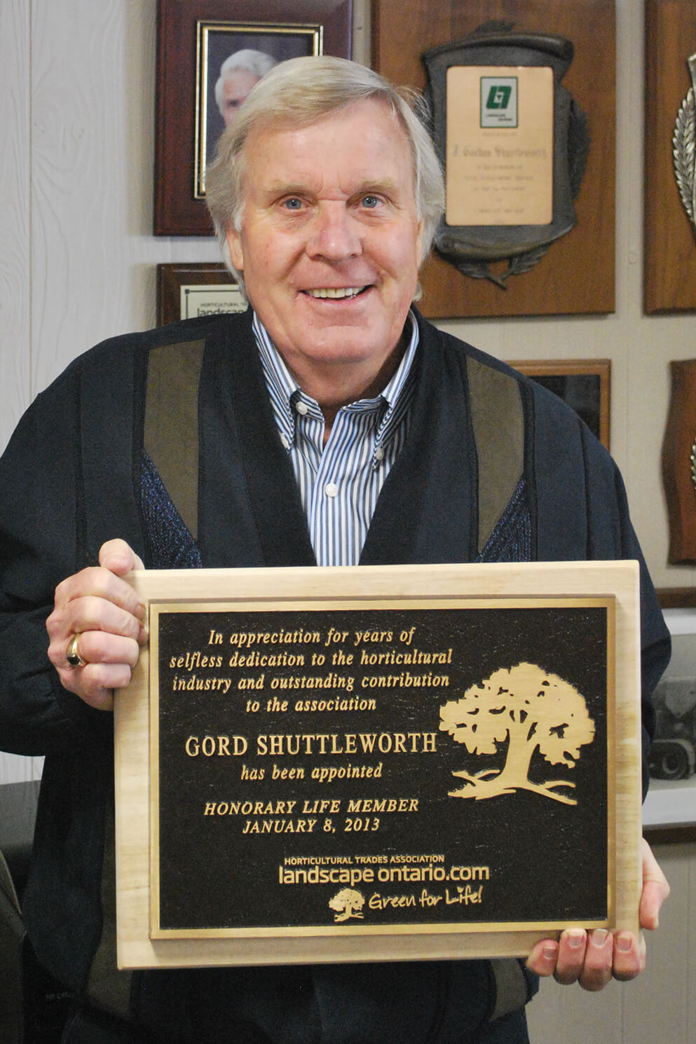 man proudly holding a plaque