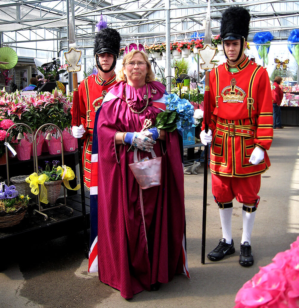 people dressed in costume in a greenhouse full of plants
