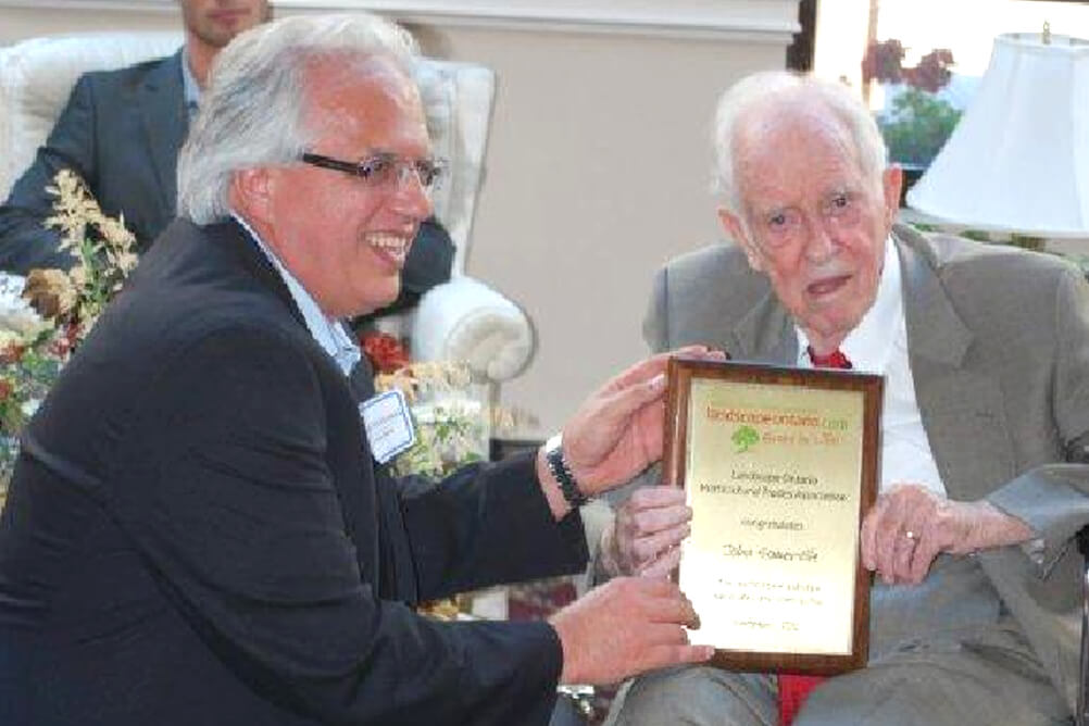 man presenting an older man with a plaque