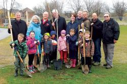 group of kids and adults posing after tree planting on arbor day