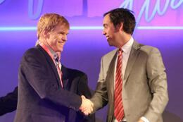 two men shaking hands on stage