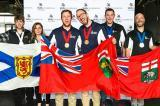 Thomas Hawley and Blaise Mombourguette (centre) hold the Ontario flag at the Skills Canada winners podium.