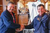 Nick Solty, left, presents Frank Solty with the trophy for fastest run of the day on the ski slopes.