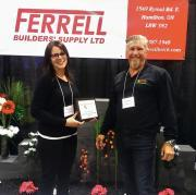 Alicia Reid and Chris DeCock from Ferrell Builders' Supply accept the best booth award.
