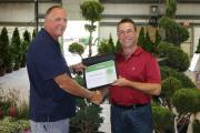 Growers Group chair John Mantel (left) presents Sheridan Nureries' Rob Naraj with a certificate for their winning entry.