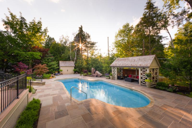 2015 - Residential Construction - $250,000 - $500,000 - This impressive view of the backyard highlights the expanse of flagstone, the inviting pavilion, the water feature and the deep, lush garden beds.