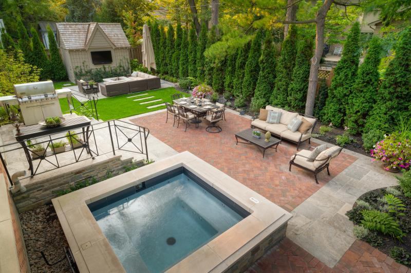 2015 - Residential Construction - $250,000 - $500,000 - This backyard was filled with many features to help the clients maximize their time at home - a four seasons gunnite hot tub, a water feature, a dining area, an alternate sitting area with fire pit, a sound system, landscape lighting, irrigation and gardens.