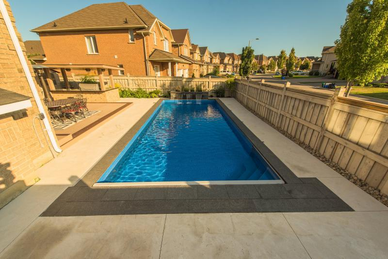 2016 - Residential Construction - $50,000 - $100,000 - Another view above the fence of the vinyl pool with a water feature wall that is also acts as a planter box