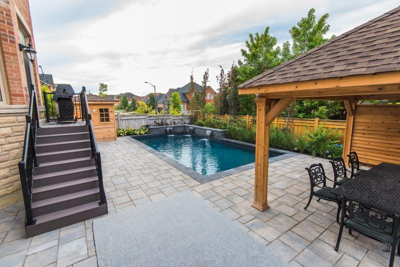 2016 - Residential Construction  - $100,000 - $250,000 - This picture was taken on top of the outdoor kitchen capturing the composite deck, custom vinyl pool, water feature, cedar shed, and part of the cedar pavilion and screen