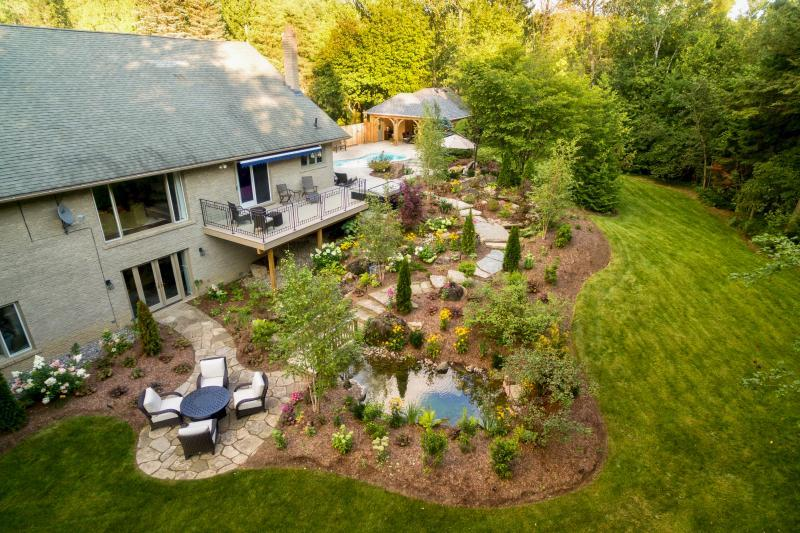 2018 - Residential Construction - $250,000 - $500,000 - After photo of completed backyard hillside area highlighting the completed water feature, winding stone staircase, flagstone terrace, planting beds and deck with completed pool terrace/cabana in background.