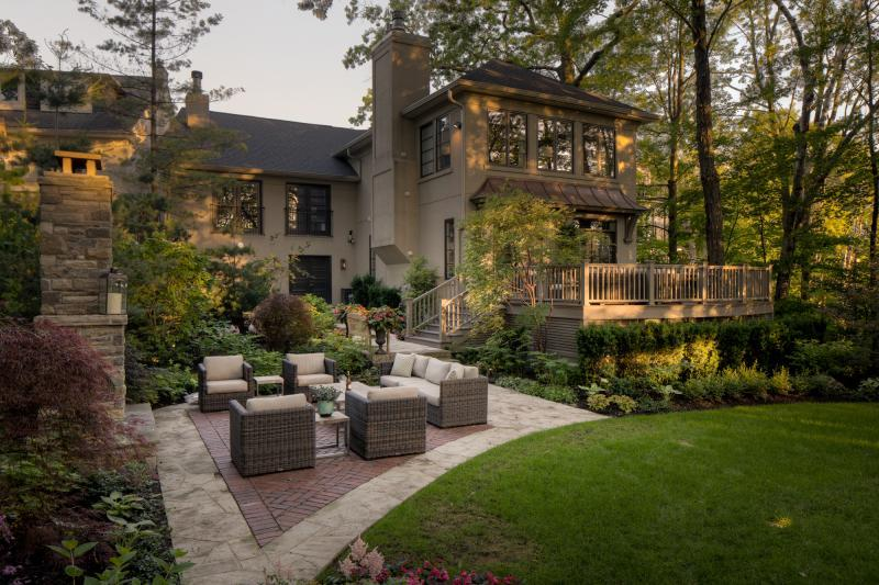 2018 - Residential Construction - $250,000 - $500,000 - A stairway down from the deck area leads through lush plantings to a large sitting area below. Flagstone was used for the patio surface with a red brick inlay to define the sitting area.
