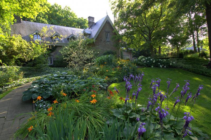 2019 - Private Residential Maintenance - 1 acre or more - a late afternoon photo catches the sun reflecting off the slate roof of the house. The close up of the dark purple hosta flowers are at their peak
