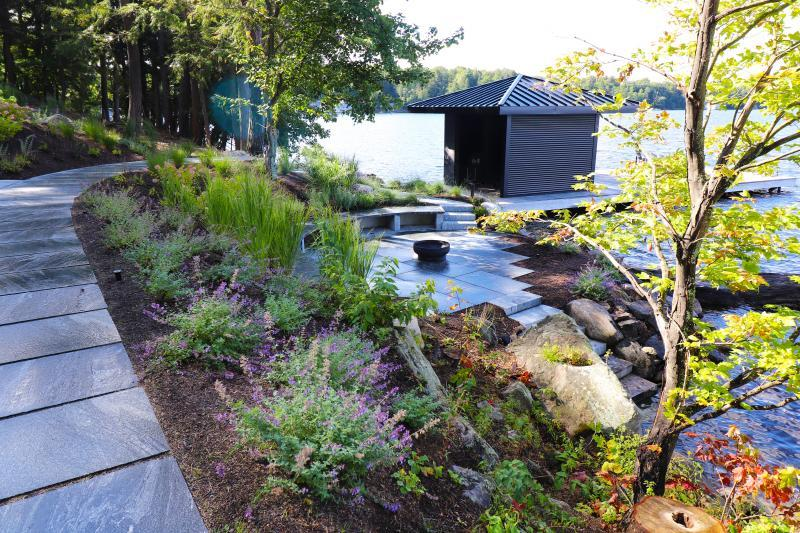 2019 - Residential Construction - $250,000 - $500,000 - Lakeside fire pit area nestled into the shoreline slope.