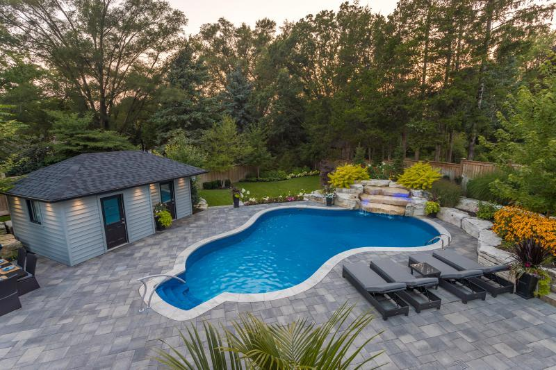 2019 - Residential Construction - $250,000 - $500,000 - View from upper deck of pool with flagstone coping, water feature, cabana, lounge area and planting.  Their is custom blue lighting on the water feature that gives it a unique glow at night